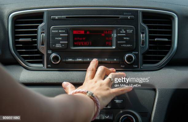 cropped hand of woman operating radio in car - radio stock pictures, royalty-free photos & images