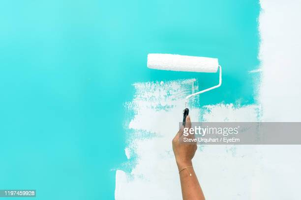 cropped hand of woman painting with roller wall - paint roller stock pictures, royalty-free photos & images