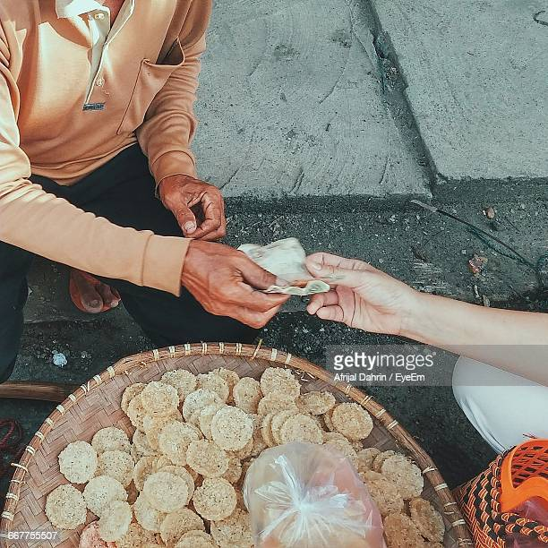 Cropped Hand Of Woman Paying Money To Seller At Market Stall