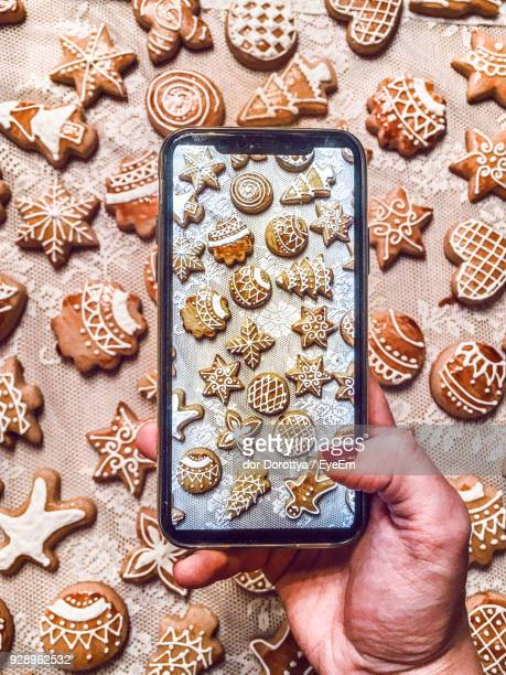 Cropped Hand Of Woman Photographing Cookies With Mobile Phone On Table