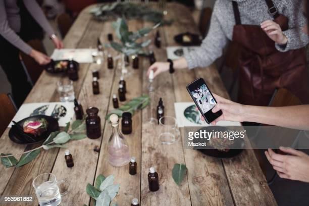 cropped hand of woman photographing table by female colleague standing at perfume workshop - onderste deel stockfoto's en -beelden