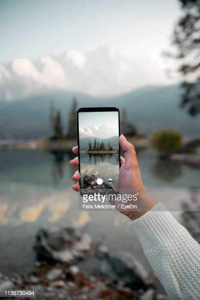 cropped hand of woman photographing with mobile phone against lake - photo messaging stock pictures, royalty-free photos & images