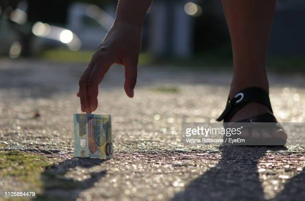 cropped hand of woman picking up paper currency on road - low section stock pictures, royalty-free photos & images