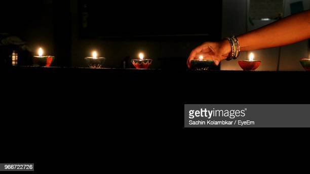 cropped hand of woman placing lit diya on retaining wall at night - putting stock pictures, royalty-free photos & images