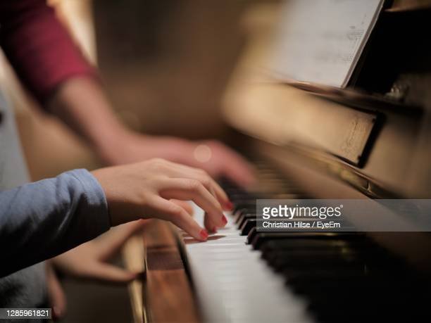 cropped hand of woman playing piano at home - christian hilse stock-fotos und bilder