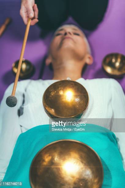 cropped hand of woman playing singing bowl for customer in spa - rin gong stock pictures, royalty-free photos & images