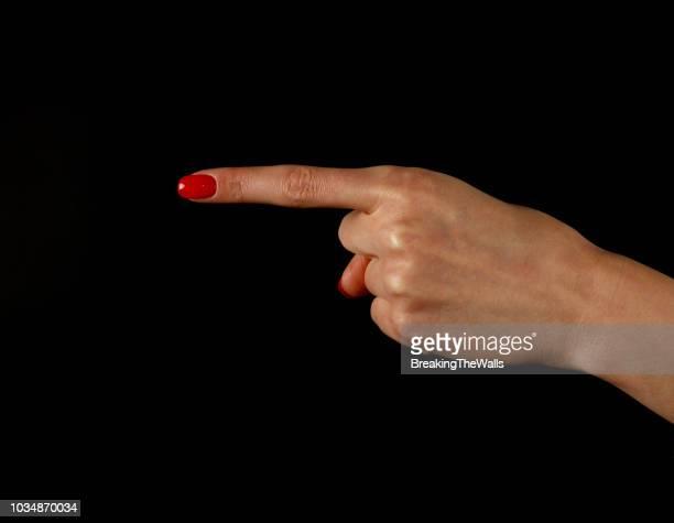 cropped hand of woman pointing against black background - wijzen handgebaar stockfoto's en -beelden