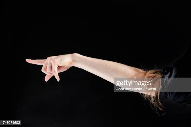 Cropped Hand Of Woman Pointing Against Black Background