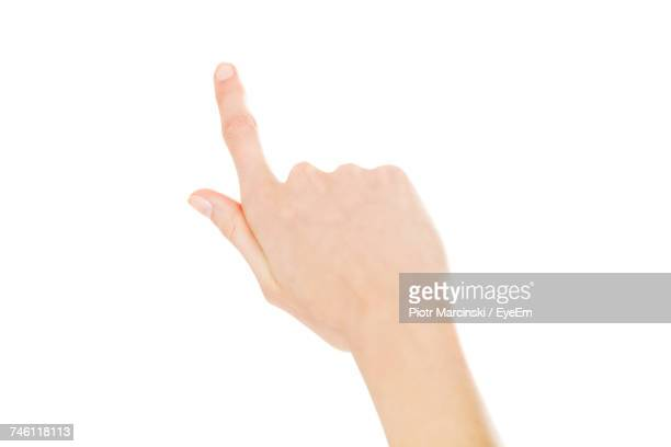 Cropped Hand Of Woman Pointing Against White Background