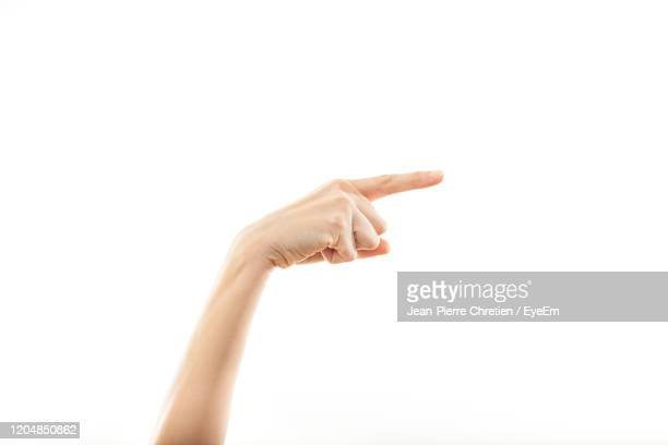 cropped hand of woman pointing over white background - mit dem finger zeigen stock-fotos und bilder