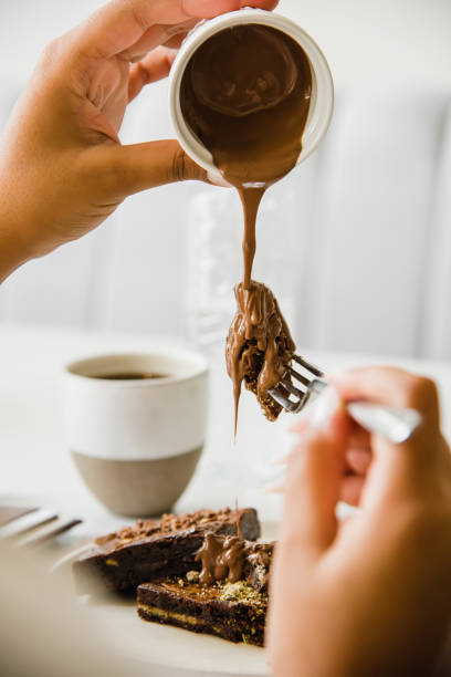 Cropped hand of woman pouring chocolate sauce on dessert