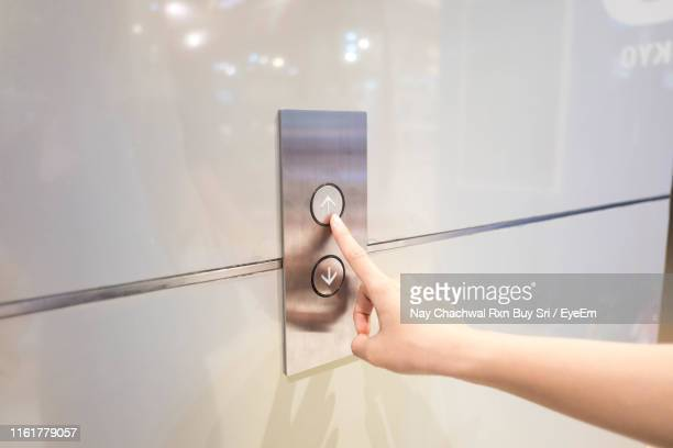 cropped hand of woman pressing push button for elevator on wall - push button stock pictures, royalty-free photos & images