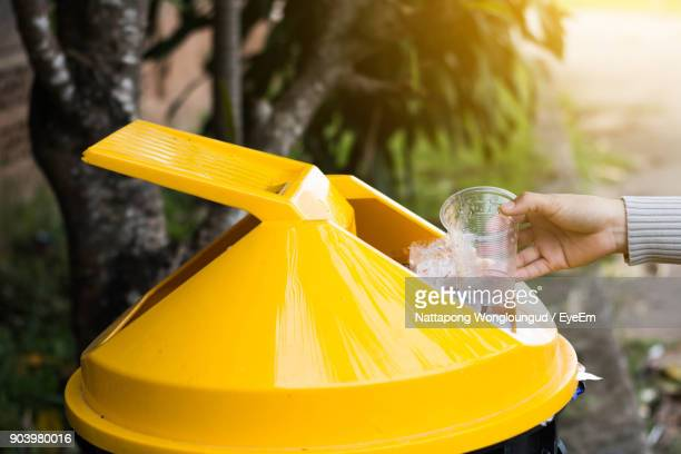 Cropped Hand Of Woman Putting Drinking Glass In Garbage Can