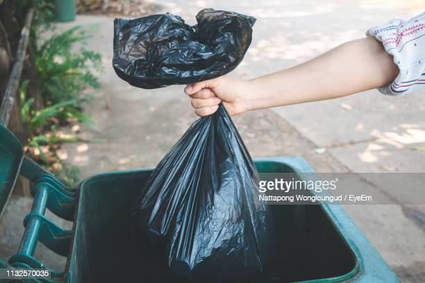 cropped hand of woman putting plastic bag in dustbin - garbage bin stock pictures, royalty-free photos & images