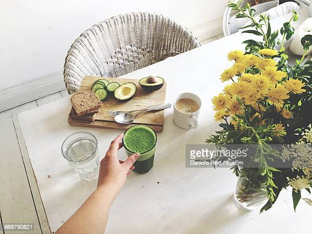 Cropped Hand Of Woman Reaching For Drink By Flowers On Table