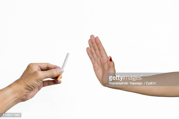 cropped hand of woman refusing cigarette over white background - stop sign stock pictures, royalty-free photos & images