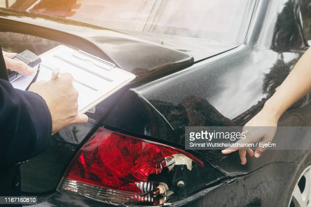cropped hand of woman showing damaged car to agent - car insurance stock pictures, royalty-free photos & images