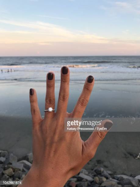 cropped hand of woman showing wedding ring at beach against sky during sunset - engagement ring stock pictures, royalty-free photos & images