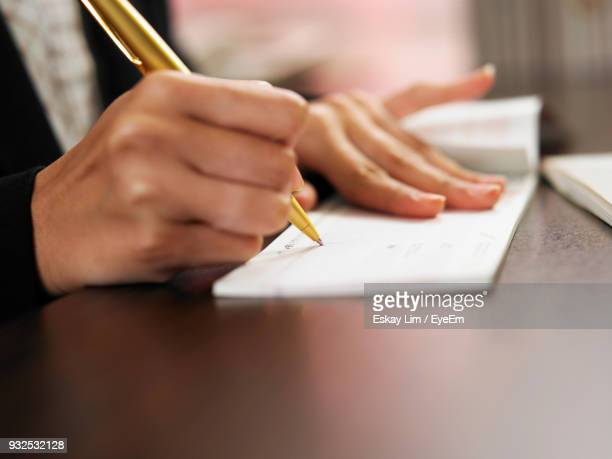 cropped hand of woman signing on check over table - handwriting stock pictures, royalty-free photos & images
