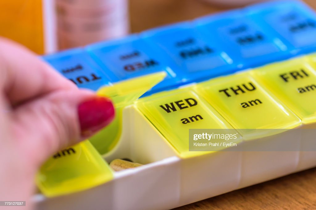 Cropped Hand Of Woman Taking Pills In Container With Text On Table : Photo