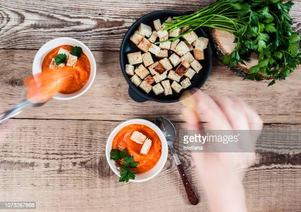 cropped hand of woman topping pumpkin soup with croutons, blurred motion - crouton stock photos and pictures