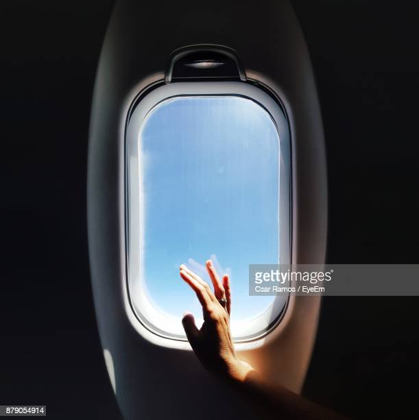 cropped hand of woman touching airplane window - avion fotografías e imágenes de stock