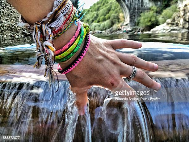 Cropped Hand Of Woman Touching Flowing Water In River