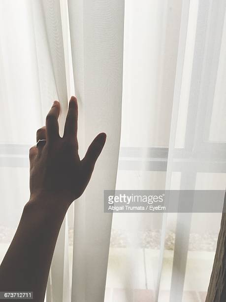 Cropped Hand Of Woman Touching White Curtain At Home