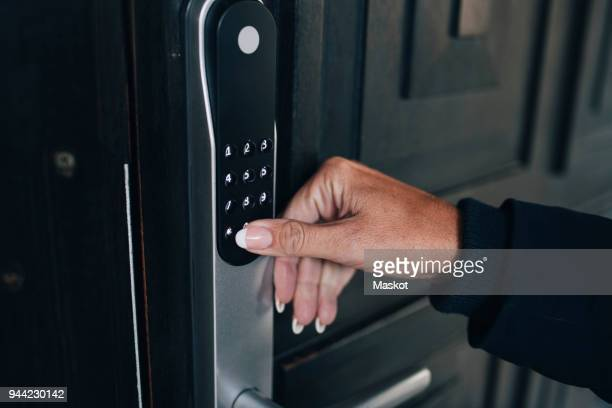 cropped hand of woman unlocking combination security code on house door - security system stock pictures, royalty-free photos & images
