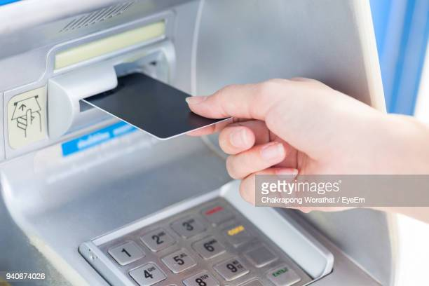 cropped hand of woman using atm - inserting stock pictures, royalty-free photos & images