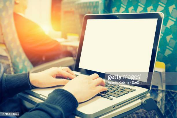 Cropped Hand Of Woman Using Laptop
