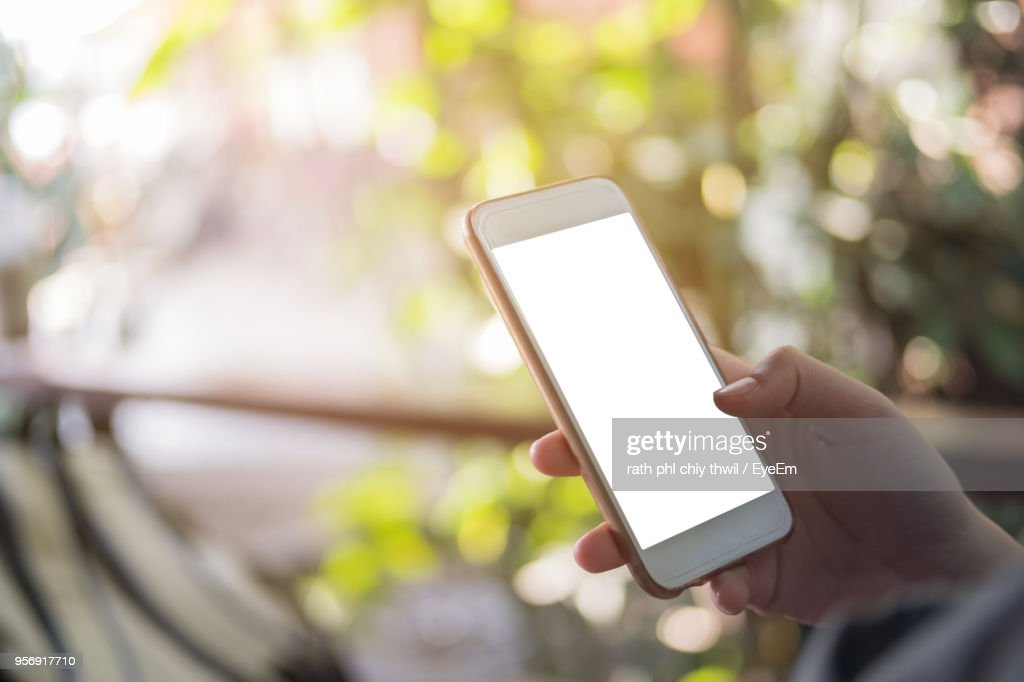 Cropped Hand Of Woman Using Mobile Phone In Balcony : Stock Photo