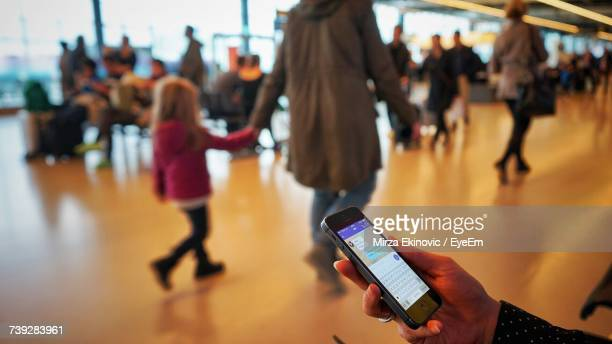 Cropped Hand Of Woman Using Phone Against People At Airport