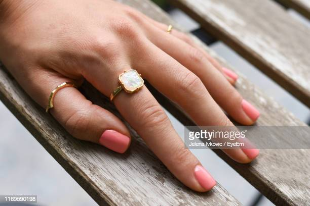 cropped hand of woman wearing ring on table - jelena ivkovic stock pictures, royalty-free photos & images