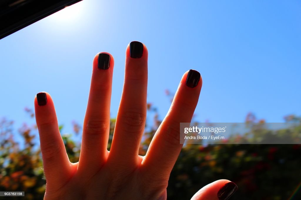 Cropped Hand Of Woman With Black Nail Polish Against Clear Sky Stock ...