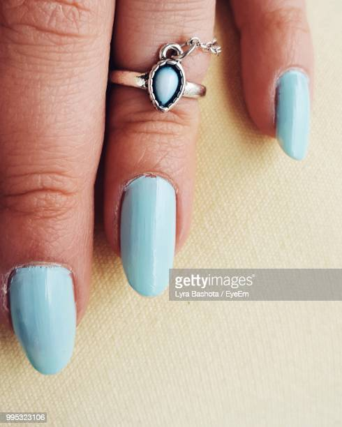 Cropped Hand Of Woman With Blue Nail Polish On Table