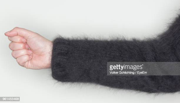 Cropped Hand Of Woman With Clinched Fist White Background