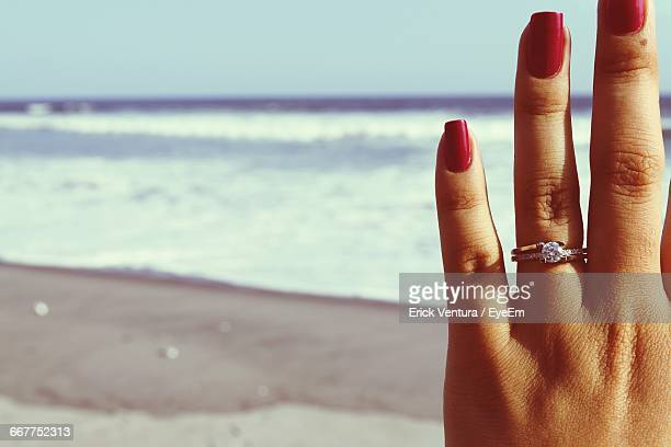 cropped hand of woman with engagement ring at beach - coastal feature stock pictures, royalty-free photos & images