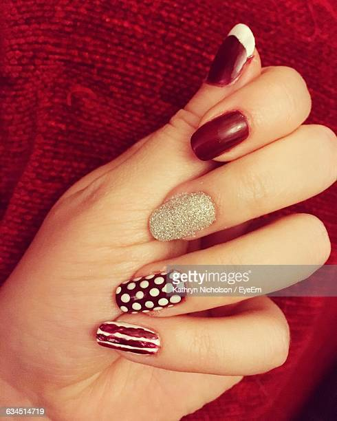 Cropped Hand Of Woman With Nail Art Against Red Fabric