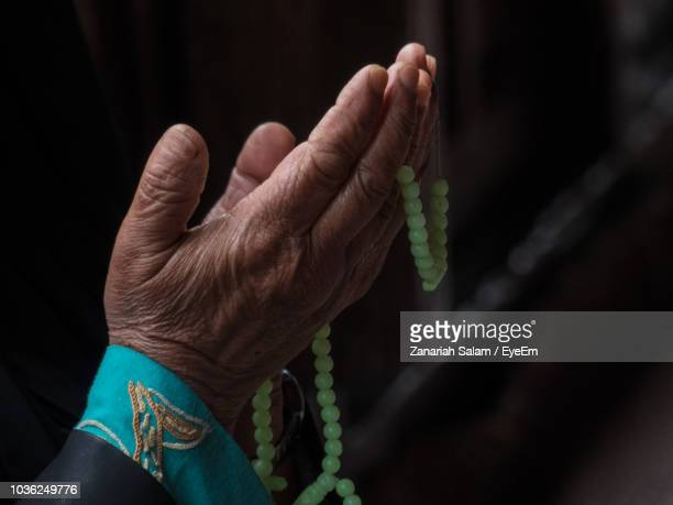 cropped hand of woman with necklace praying in darkroom - kashmir valley stock pictures, royalty-free photos & images