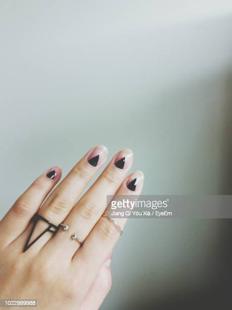 cropped hand of woman with painted nails against wall - nail art stock pictures, royalty-free photos & images