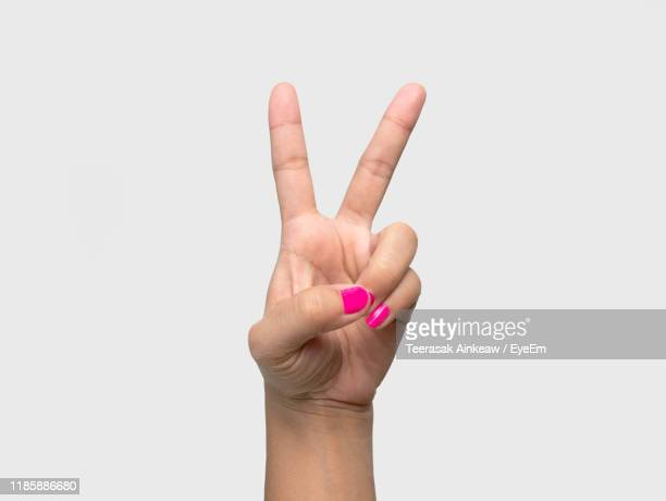 cropped hand of woman with pink nail polish gesturing peace sign against white background - pace foto e immagini stock