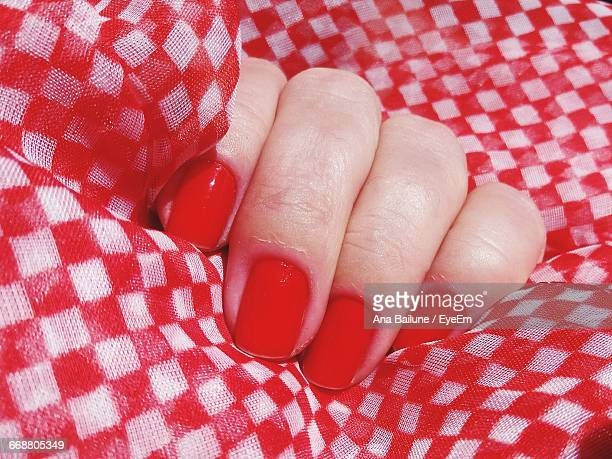 Cropped Hand Of Woman With Red Nail Polish Holding Fabric