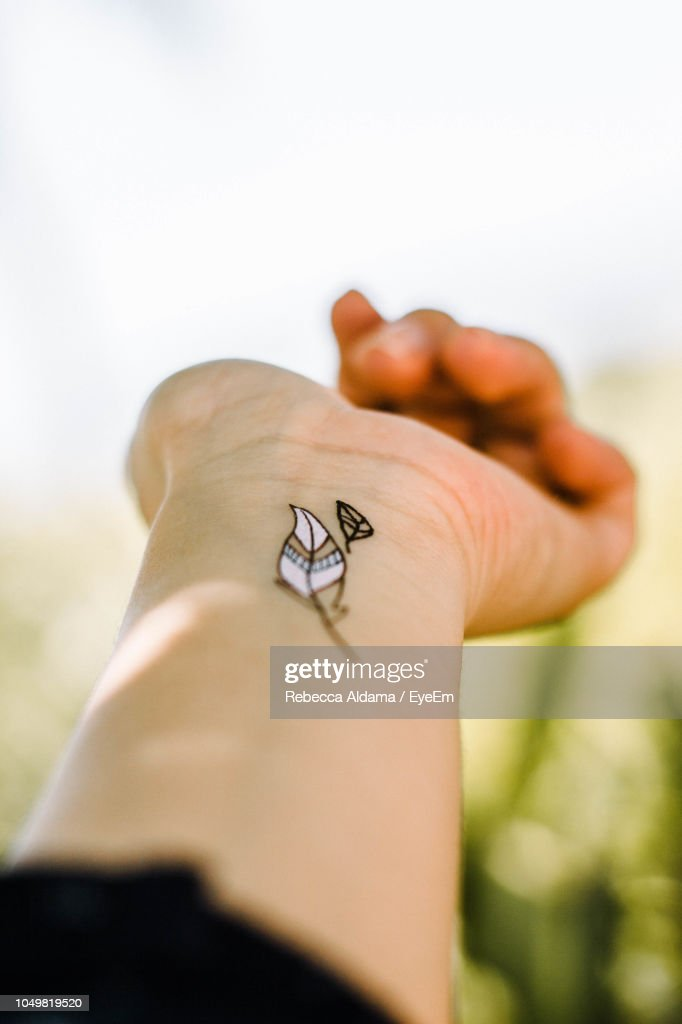 Cropped Hand Of Woman With Tattoo Against Clear Sky : Stock Photo