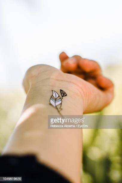 Cropped Hand Of Woman With Tattoo Against Clear Sky