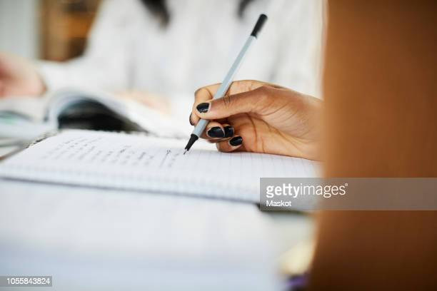 cropped hand of woman writing on book while studying at table - black nail polish stock photos and pictures