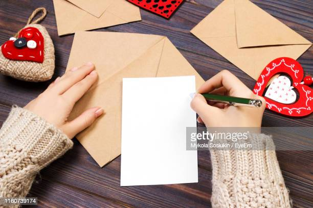 cropped hand of woman writing on paper during valentine day - manga comprida imagens e fotografias de stock