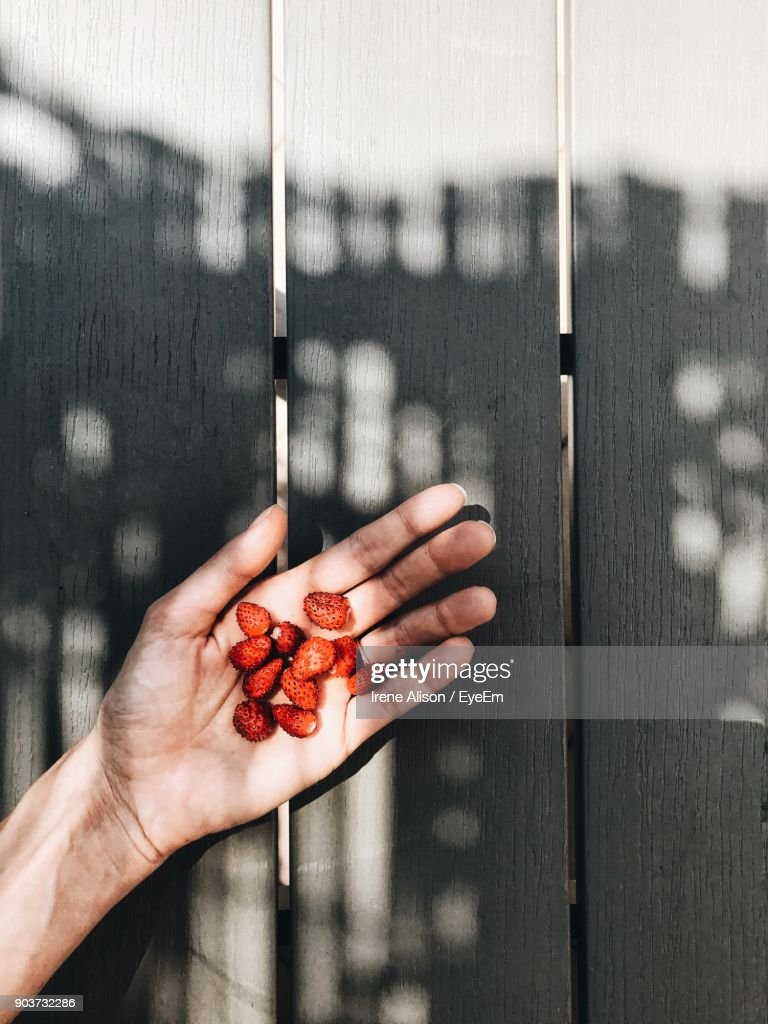 Cropped Hand Of Women Holding Fruits On Table : Photo