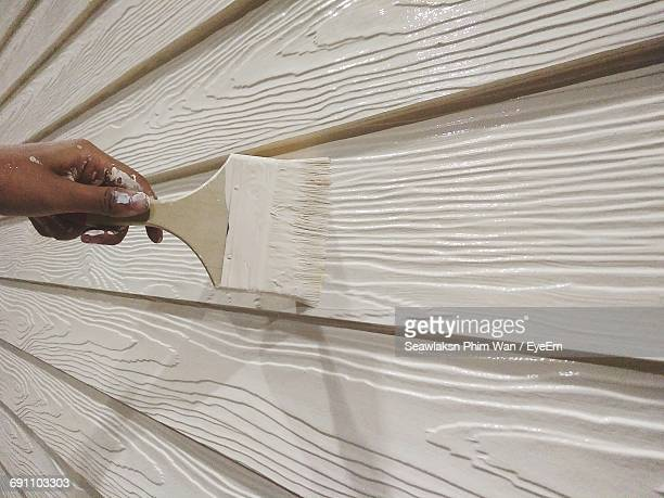 Cropped Hand Of Worker Painting Wooden Wall