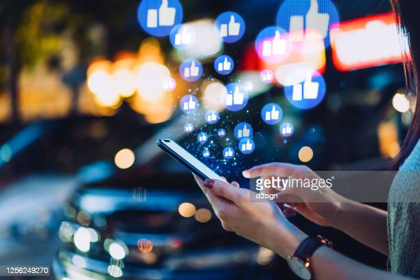 cropped hand of young asian woman using smartphone on social media network application on the go, viewing or giving likes in the city at night. social media addiction concept - multimedia stock pictures, royalty-free photos & images